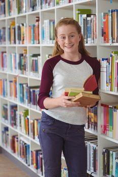 Portrait of happy schoolgirl holding books in library at school