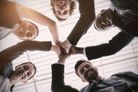 Group of happy businesspeople giving high five