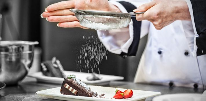 Female chef finishing a dessert plate