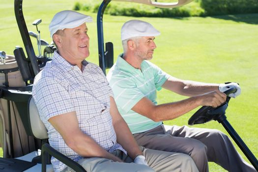 Golfing friends driving in their golf buggy on a sunny day at the golf course