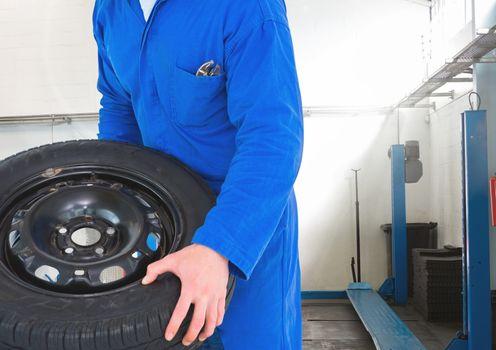 Mechanic holding tyre in repair garage