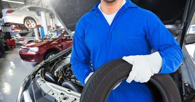 Mechanic holding tyre at garage