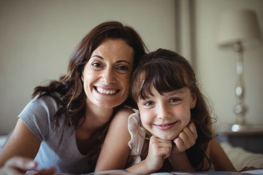 Mother and daughter smiling while lying on bed