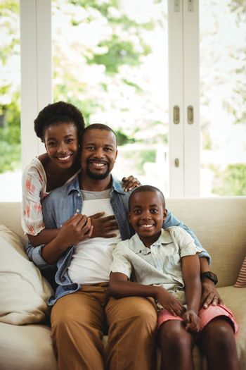 Portrait of parents and son sitting on sofa in living room