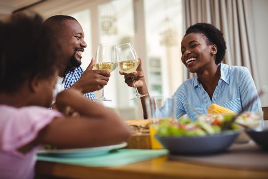 Family toasting glasses of wine while having meal on dining table at home