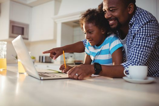 Father using laptop while assisting his daughter with homework at home
