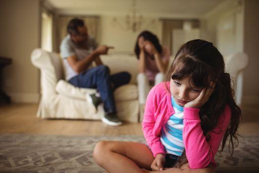 Sad girl listening to her parents arguing