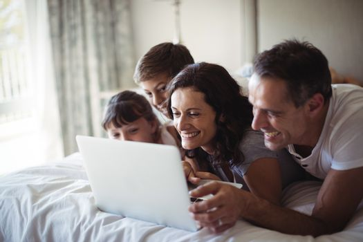 Happy family using laptop on bed in bedroom at home