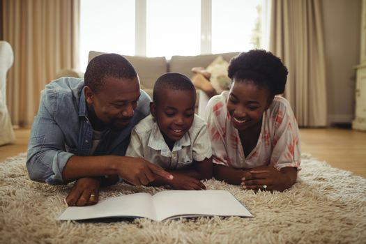 Parents and son reading a book while lying on a rug