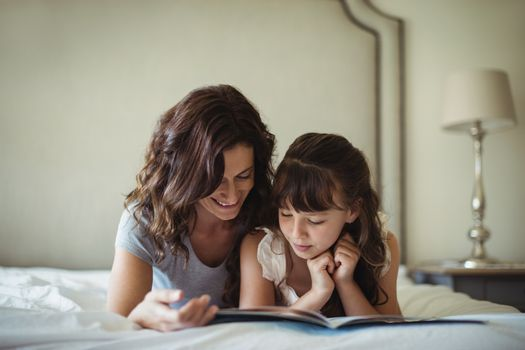 Mother and daughter reading a book while lying on bed