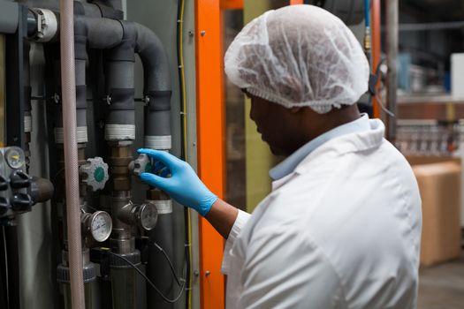 Factory engineer monitoring a pressure gauge in factory