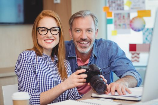 Portrait of graphic designers holding digital camera in office