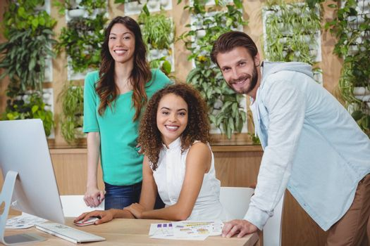 Team of graphic designers smiling at desk in office