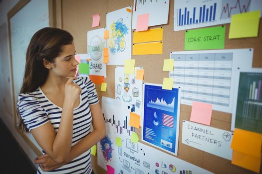 Female executive looking at bulletin board in office