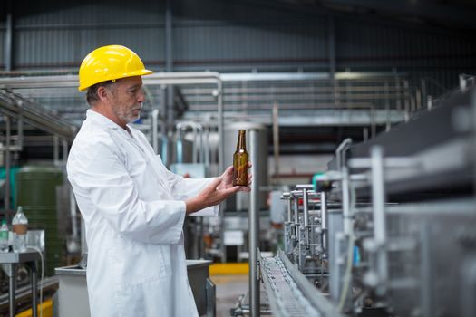 Factory worker examining a bottle in factory