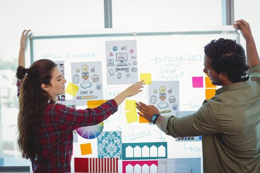 Male and female graphic designers discussing over sticky notes in office