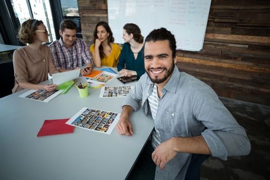 Portrait of smiling graphic designer sitting in office while colleague discussing in background