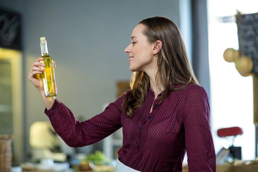 Shop assistant looking at olive oil bottle in grocery shop