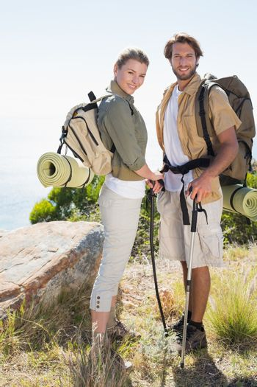 Hiking couple smiling at camera at mountain summit