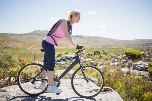 Fit pretty cyclist on a rocky terrain