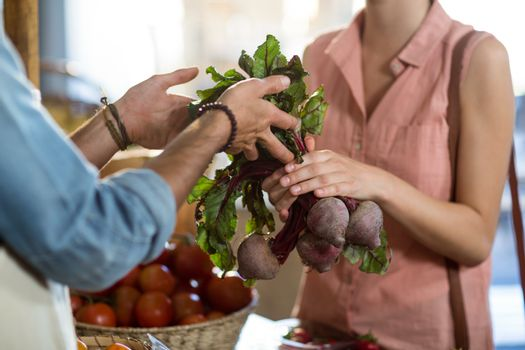 Woman taking beetroot from the vendor at the grocery store