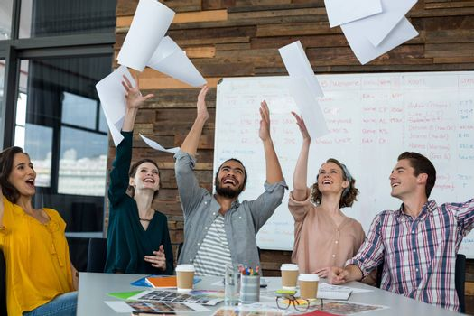 Team of excited graphic designers throwing document in the air during meeting at office
