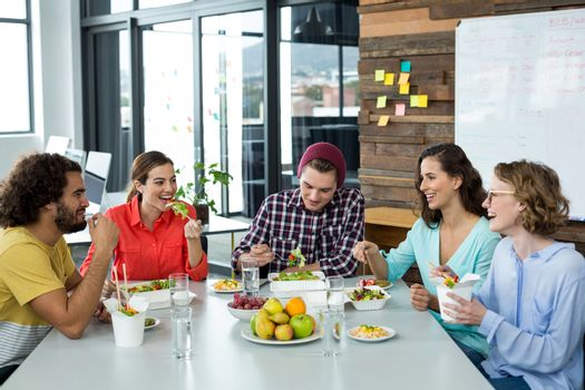 Smiling business executives interacting while having meal in office