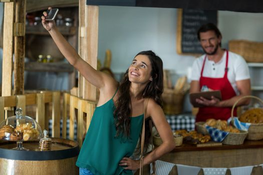 Smiling woman talking selfie with mobile phone at counter in bake shop