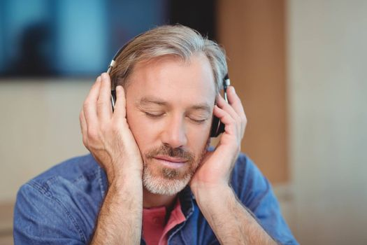 Male graphic designer listening music on headphones in office