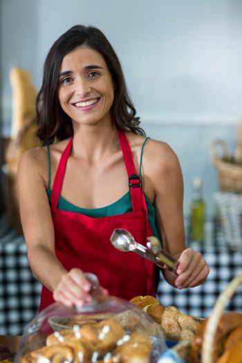 Portrait of smiling female staff holding tongs at counter