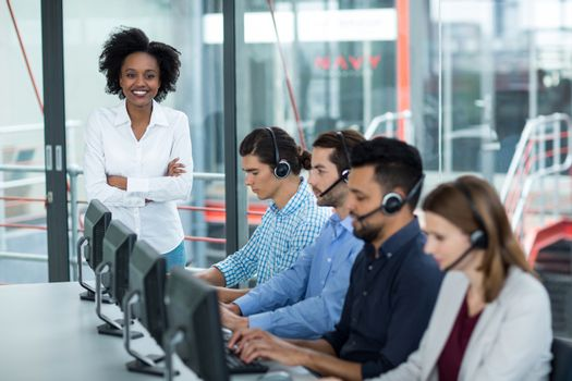 Smiling Businesswoman standing with arms crossed while colleagues talking on headset in office