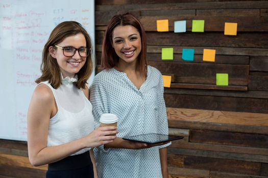 Portrait of business executives standing with digital tablet and coffee cup in office
