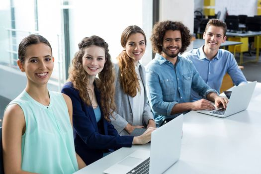 Portrait of smiling business team discussing over laptop in meeting at office