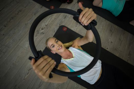 Fit woman exercising with pilates ring
