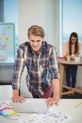 Male graphic designer leaning on table and using laptop in office