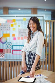 Portrait of female graphic designer using digital tablet at desk in office