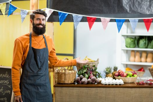 Vendor pointing towards counter in grocery store