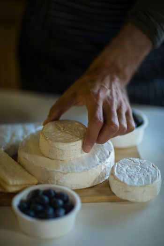 Salesman arranging cheese at counter