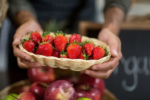 Vendor holding a basket of strawberries at the grocery store