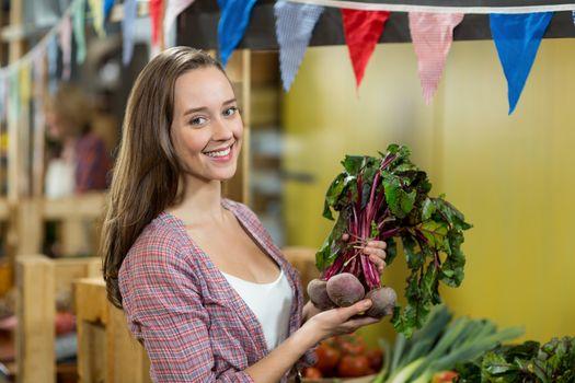 Smiling woman choosing vegetables in grocery store