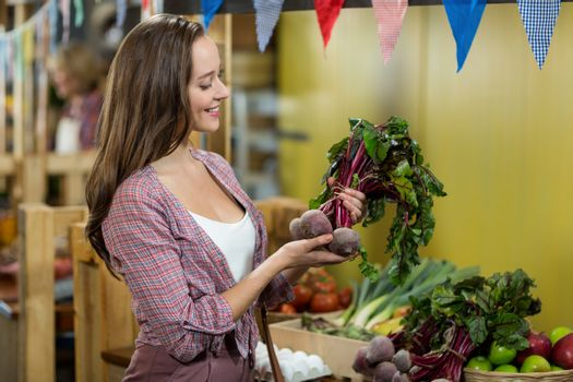 Woman choosing vegetables in grocery store