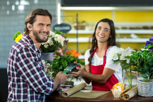 Florist receiving a payment by credit card from the customer in the florist shop