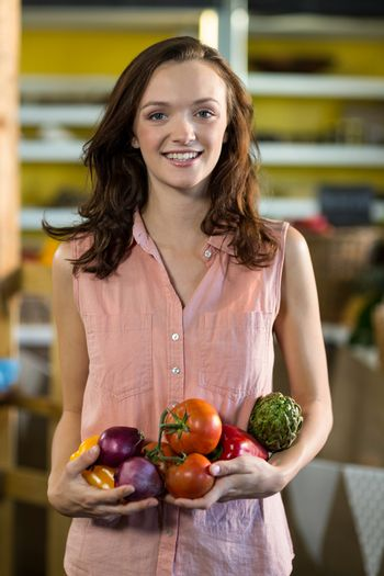 Woman holding vegetables at grocery store