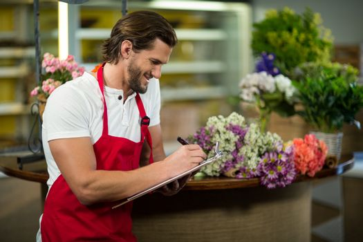 Florist writing on the clipboard