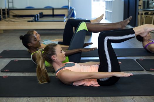 Women performing stretching exercise in gym