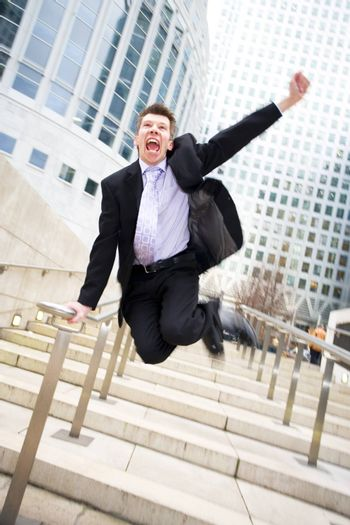 Happy caucasian businessman leaving the office jumping in the air themes of celebration joy winner