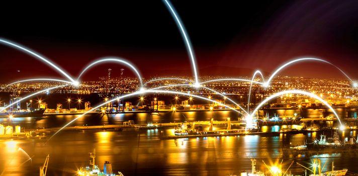 Illuminated harbor against cityscape