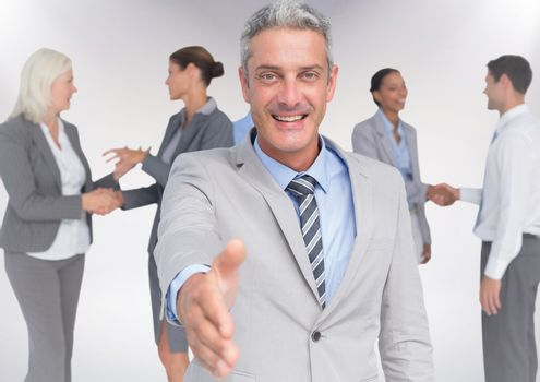 Digital composite of Handshake in front of business people with white background