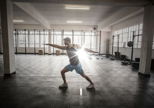 Digital composite of Man stretching in gym with flare