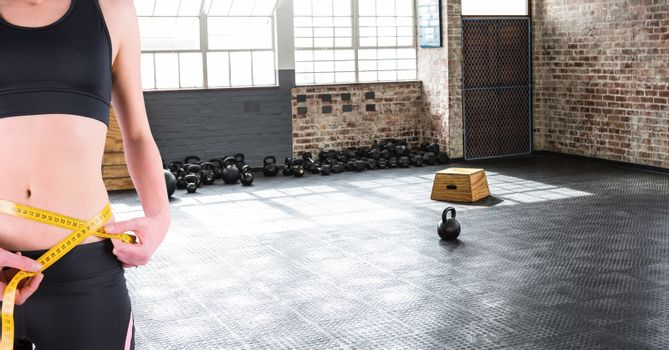 Fitness woman Torso measuring her size in a gym